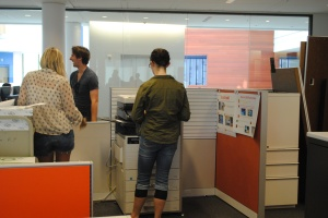 Students waiting for their documents to print out at the new Swipe-to-Print station in the Information commons. (Photo: Rachel Brustein)