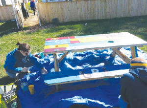 Rachel Brustein '16 and others paint a picnic table and enjoying the sunlight at the Goucher Community Garden during Harvest Fest (Photo: Jonathan Trauner)