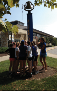 Women's Cross Country Team ringing the victory bell outside of the Decker Sports Center, (Photo: Christine Cherry)